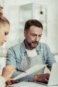 Respondiendo cartas. apuesto hombre concentrado sentado cerca de su asistente y escribiendo un correo electrónico a su socio comercial.