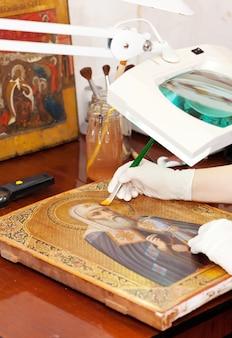 Restaurador trabaja en el antiguo icono de oro