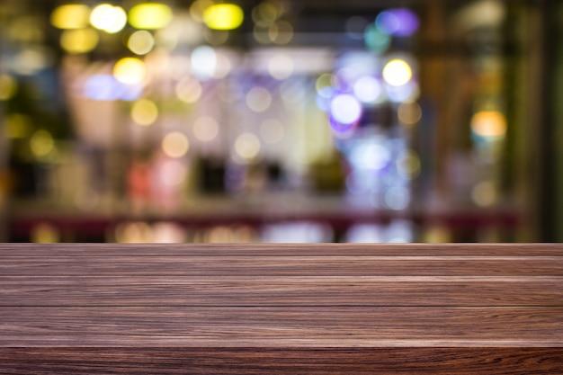 Restaurante de café de la falta de definición o cafetería vacía de la mesa de madera oscura con el backgro ligero del bokeh del oro