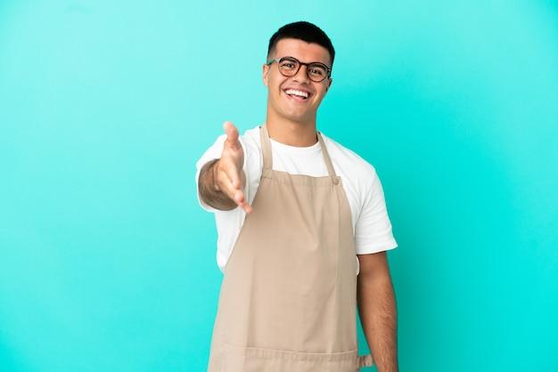 Restaurante camarero hombre sobre fondo azul aislado un apretón de manos para cerrar un buen trato