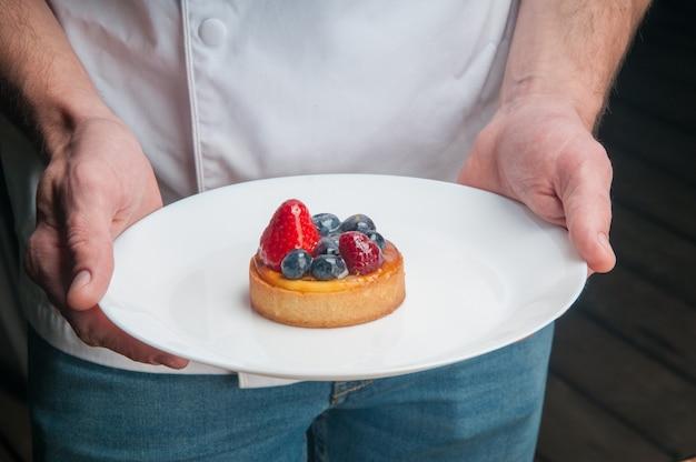 Restaurante chef sosteniendo plato con postre dulce