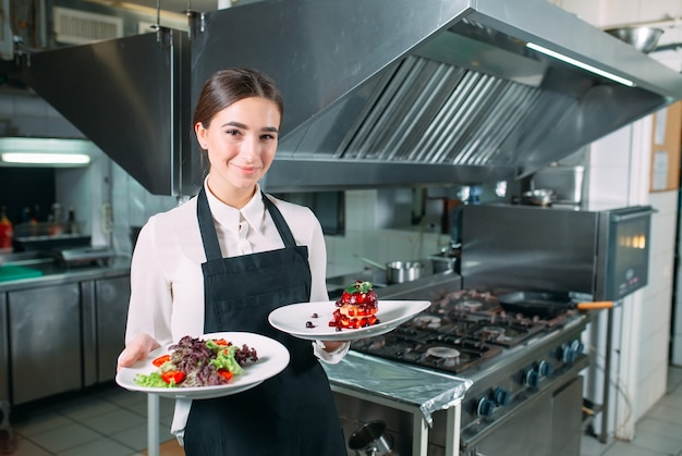 Restaurante cocina. camarero con un plato listo foie gras posando en el fondo de la cocina.