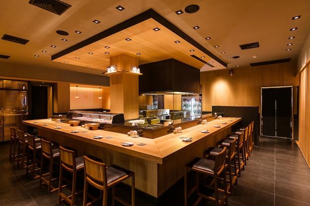 Restaurante japonés de brochetas a la parrilla yakitori con barra de bar alrededor del área de la cocina a la parrilla. principalmente decorado con textura de madera de roble.