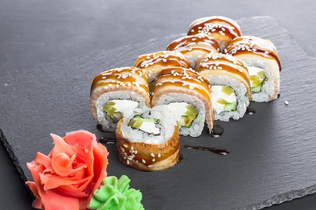 Restaurante japonés, sushi roll en placa de pizarra negra.