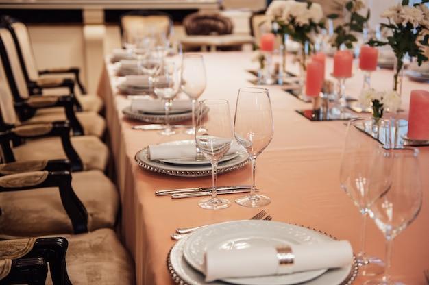 Restaurante de lujo. interior lujoso, mesas blancas, platos y vasos para los invitados.