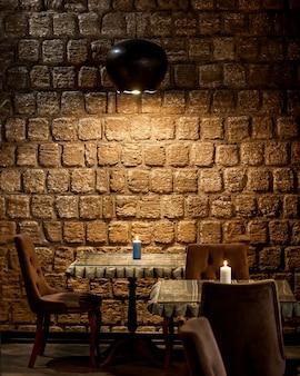 Restaurante con paredes de piedra e iluminación superior.