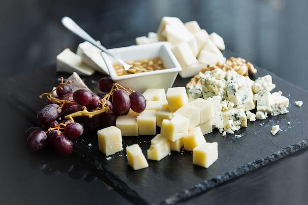 Restaurante plato de queso con salsa. varios tipos de quesos con uva sobre piedra pizarra negra.