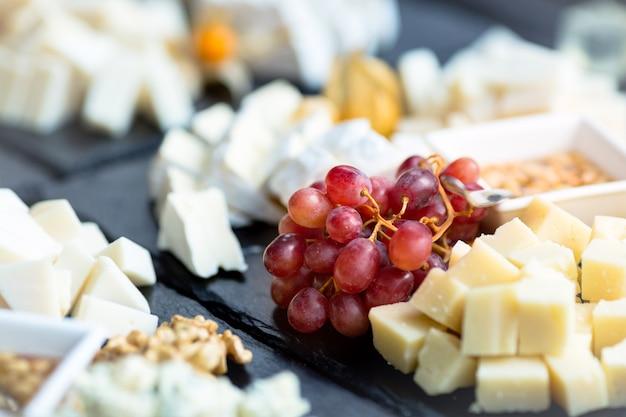 Restaurante plato de queso. varios tipos de quesos con uva sobre piedra pizarra negra.