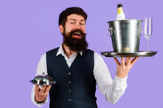 Restaurante de servicio, camarero con bandeja de servicio con enfriador de vino y campana metálica.
