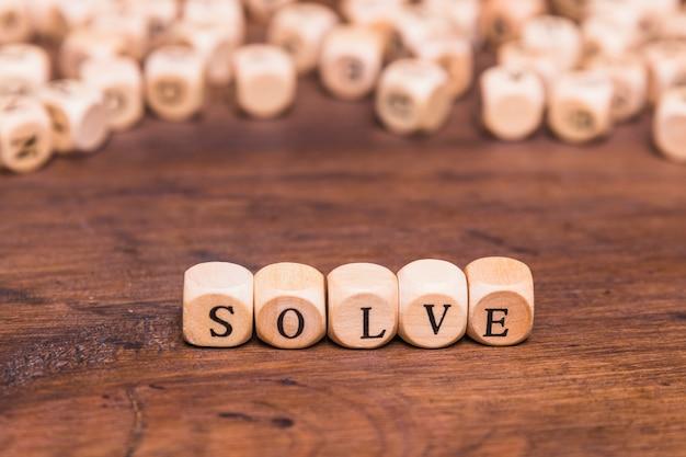Resuelve la palabra en cubos de madera sobre mesa marrón
