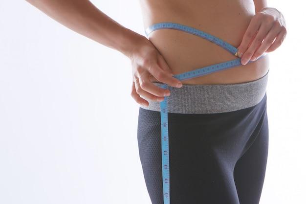 Resultado de ejercicios deportivos: un primer plano de estómago tonificado sobre un fondo blanco. la niña mide su cintura con una cinta de centímetros.