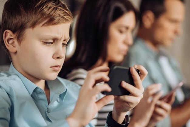 Resultado frustrante. lindo niño haciendo pucheros y decepcionado por el resultado del juego mientras sus padres usan sus teléfonos en el fondo