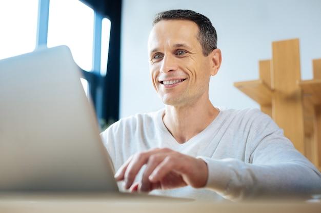 Resultados exitosos. alegre empresario ambicioso positivo mirando la pantalla del portátil y sonriendo mientras ve resultados exitosos