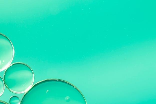 Resumen aceite cae en agua sobre fondo verde