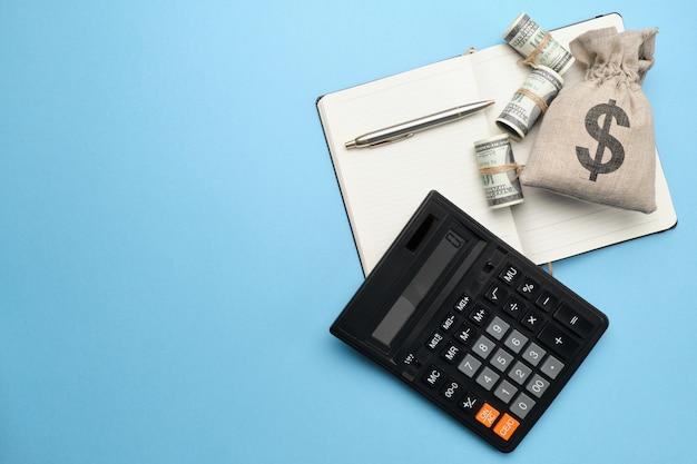 Resumen bolsa con dinero, calculadora, bolígrafo y diario sobre un fondo azul con espacio de copia