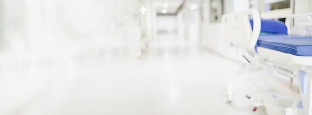 Resumen borrosa camino del pasillo del hospital con cama de paciente en blanco para el servicio de pantalla panorámica