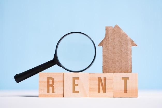 Resumen casa de cartón, lupa de vidrio en cubos con la palabra alquiler. búsqueda de vivienda, la legalidad de la transacción.