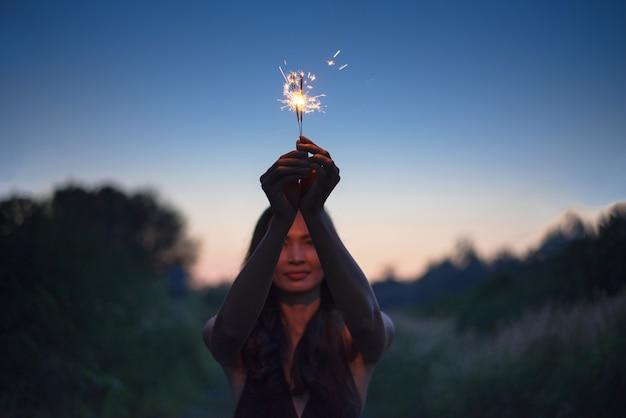 Resumen desenfoque de bengalas para celebración, movimiento por viento borrosa mano de mujer sosteniendo ardiente brillo navideño en la naturaleza y el cielo crepuscular