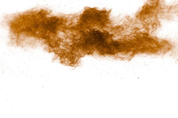 Resumen explosión de polvo marrón oscuro sobre fondo blanco. congelar movimiento de salpicaduras de polvo marrón.