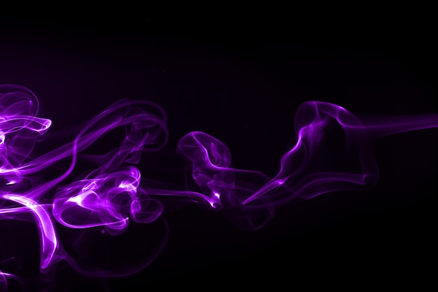 Resumen de humo púrpura sobre fondo negro. tinta de color de agua