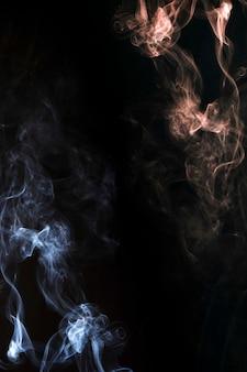 Resumen de humo que sopla en la esquina del fondo oscuro