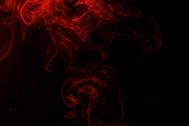 Resumen de humo rojo sobre fondo negro
