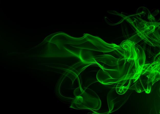 Resumen de humo verde sobre fondo negro, concepto de oscuridad