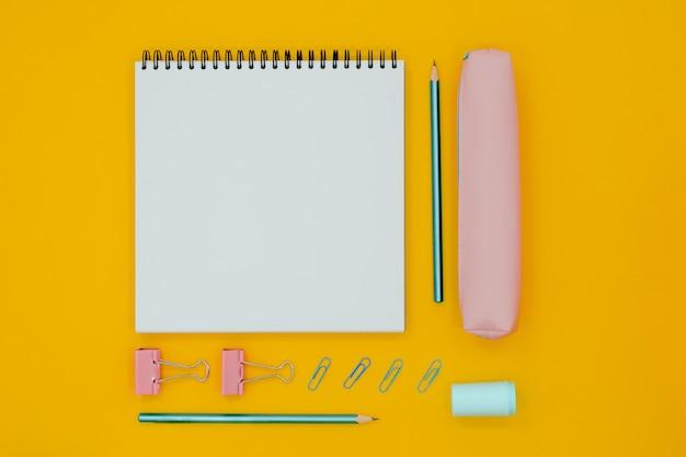 Resumen mesa roja con papelería. cuaderno en blanco y tijeras, pensils, bolígrafos. flatlay superior horizontal vista copyspace.