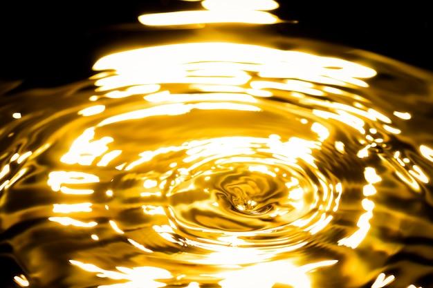 Resumen de metal dorado líquido, gotas de agua olas y ondas
