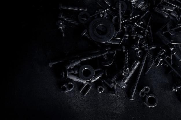 Resumen de tuercas metálicas usadas y pernos de clavo sobre fondo oscuro