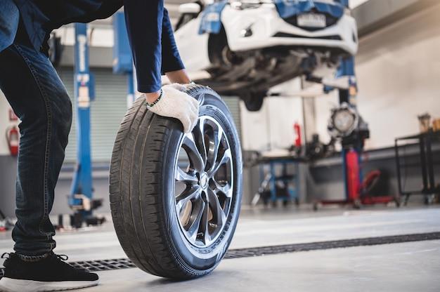 Retención mecánica masculina y neumático rodante en el fondo del taller de reparación