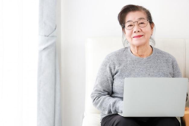 Retiro asiático de la mujer mayor que usa la computadora portátil en sala de estar
