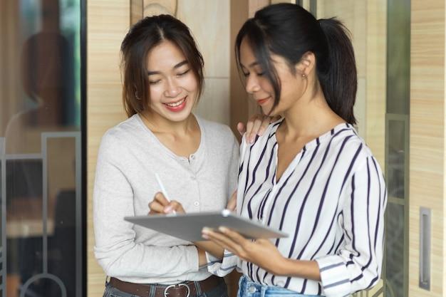 Retrato de 2 mujeres empresarias discutiendo y mirando en tableta frente a la sala de oficina