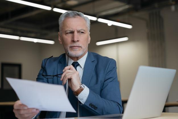 Retrato de abogado senior pensativo sosteniendo documentos comerciales