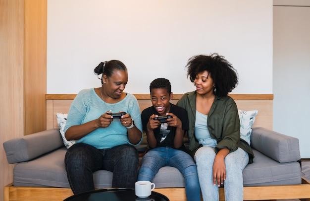 Retrato de abuela afroamericana, madre e hijo jugando videojuegos juntos en casa