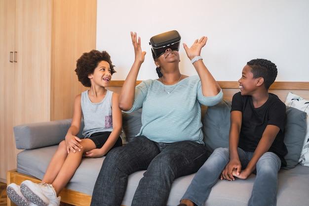 Retrato de abuela afroamericana y nietos jugando junto con gafas vr en casa. concepto de familia y tecnología.