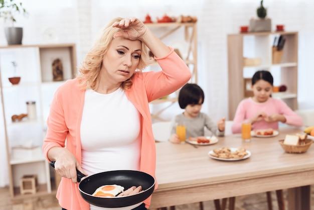 Retrato de abuela cansada sosteniendo pan con huevos