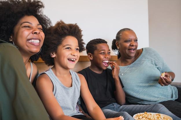 Retrato de abuela, madre e hijos afroamericanos viendo una película y comiendo palomitas de maíz mientras está sentado en el sofá en casa. concepto de familia y estilo de vida.