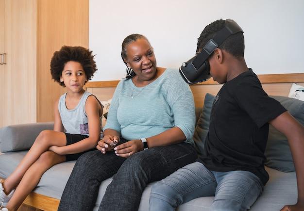Retrato de abuela y nietos afroamericanos jugando junto con gafas vr en casa. concepto de familia y tecnología.