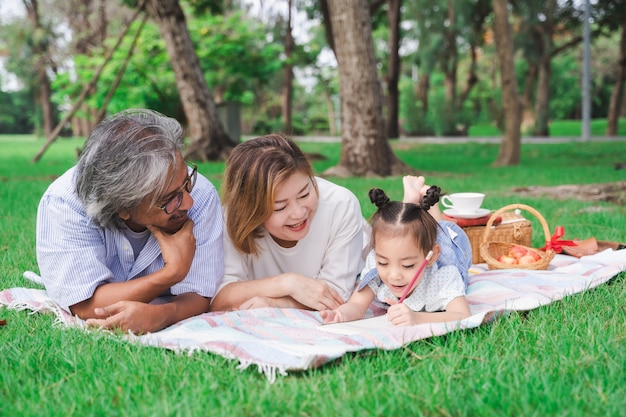 Retrato de abuelos asiáticos y nieta tendida en el campo de vidrio verde al aire libre, familia disfrutando de picnic juntos en concepto de día de verano