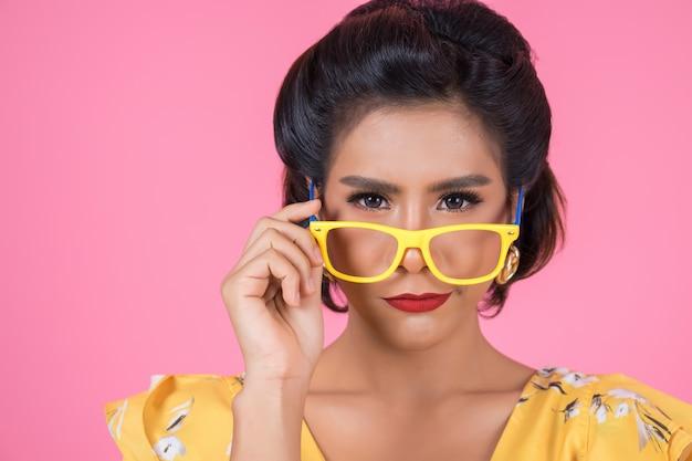 Retrato de acción de mujer de moda con gafas de sol.