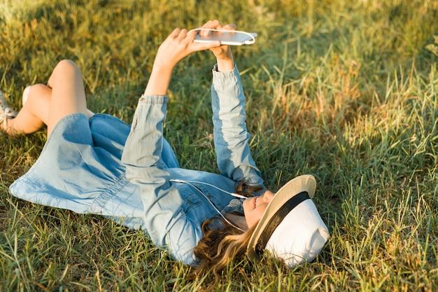 Retrato de adolescente de 14 años tumbado en la hierba.