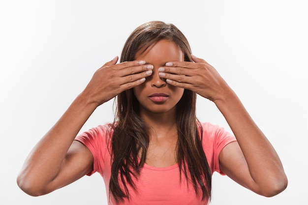 Retrato de una adolescente africana cubriendo sus ojos