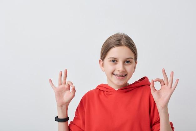 Retrato de una adolescente con aparatos dentales vistiendo una sudadera con capucha roja que muestra el signo de ok