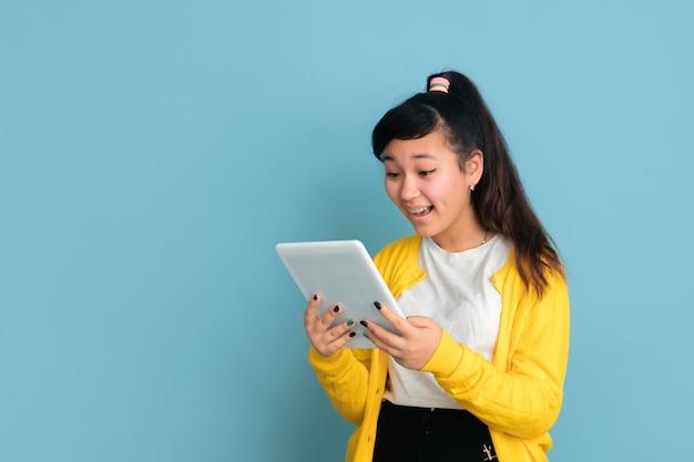 Retrato de adolescente asiático aislado sobre fondo azul studio