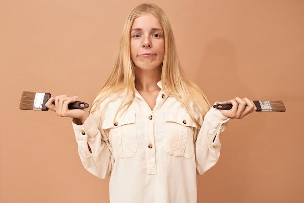 Retrato de una adolescente bonita con tirantes y cabello largo usando herramientas especiales mientras pinta las paredes interiores para protegerlas de daños por agua o corrosión