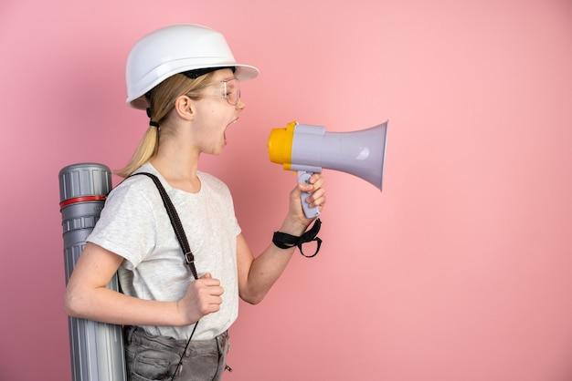 Retrato de una adolescente en un casco, un altavoz en sus manos y un sombrero de copa en la espalda