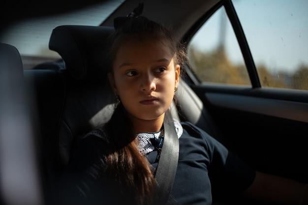 Retrato de una adolescente con cinturón de seguridad en el coche. concepto de familia.