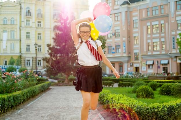 Retrato de una adolescente colegiala corriendo por la carretera