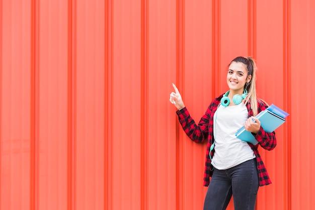 Retrato de una adolescente feliz sosteniendo libros en la mano con auriculares alrededor de su cuello apuntando el dedo contra una pared naranja